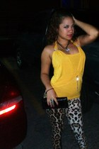 mustard top - black bag - light brown pants - black necklace - black bracelet