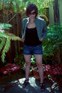 Green-jacket-black-top-blue-shorts-black-shoes-silver-necklace-brown-c