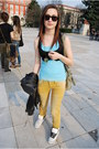 Yellow-jeans-black-sunglasses-blue-top-black-vest-owl-necklace