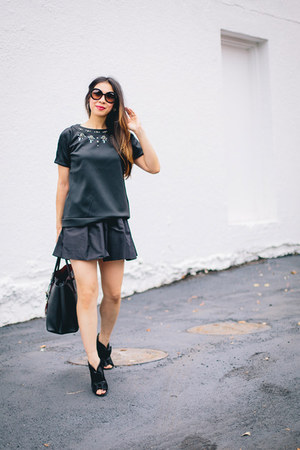 black satin Chanel boots - black leather Prada bag - black faille Miu Miu skirt