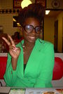 Green-blazer-black-shirt-brown-glasses-white-necklace